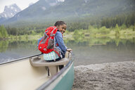 Girl with backpack in canoe at lake - HEROF07664