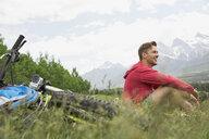 Man with mountain bike sitting in grass - HEROF07673