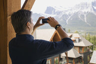 Man photographing mountains from balcony - HEROF07709
