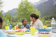 Mother and daughter eating at picnic table - HEROF07757