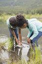 Girls catching fish in lake - HEROF07769