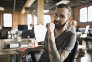 Portrait of confident businessman with tattoos in office - HEROF07796