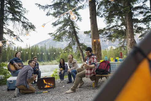 Friends hanging out around campfire at campsite - HEROF07814