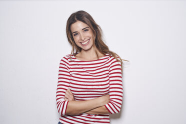 Portrait of laughing young woman wearing red-white striped shirt against white background - PNEF01166