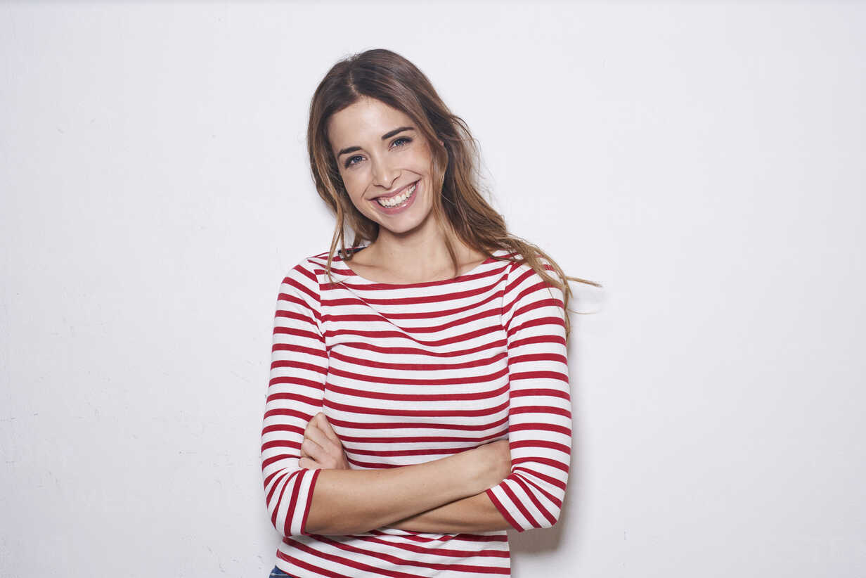 Portrait of laughing young woman wearing red-white striped shirt against white background - PNEF01166 - Philipp Nemenz/Westend61