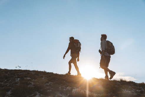 Italy, Monte Nerone (PU), two men hiking on top of a mountain, backlight view at sunset - WPEF01308