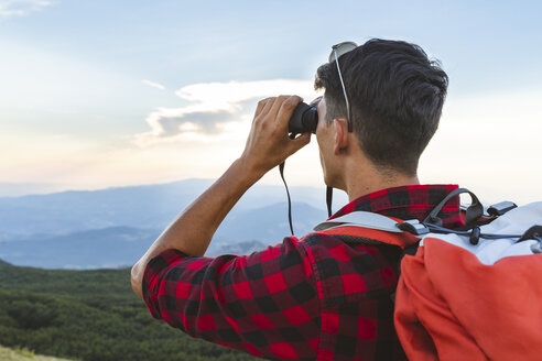 Italy, Monte Nerone (PU), hiker on top of a mountain looking with a binocular - WPEF01311