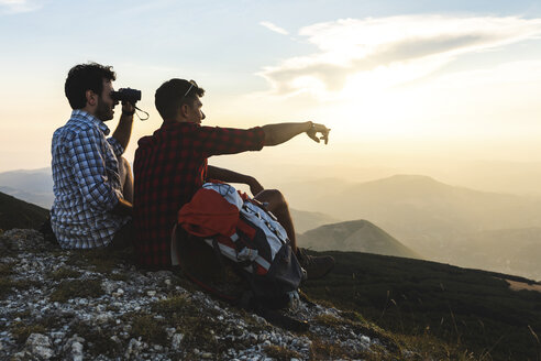 Italy, Monte Nerone, two hikers on top of a mountain enjoying the view at sunset - WPEF01314