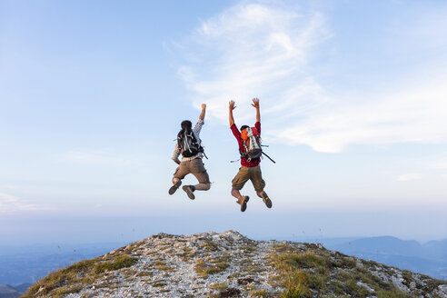 Italy, Monte Nerone, two happy and successful hikers jumping on top of a mountain - WPEF01320