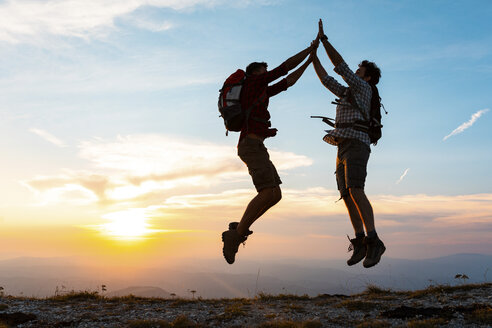 Italy, Monte Nerone (PU), happy and successful men making a jump and giving high five on top of a mountain, silhouette at sunset - WPEF01323