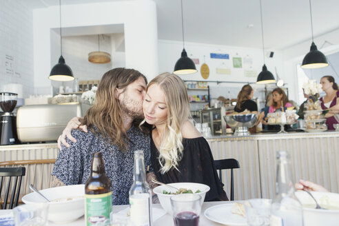 Young man kissing woman on cheek while sitting at restaurant table - ASTF02724