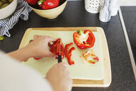 Cropped image of woman chopping red bell pepper in kitchen - ASTF02754