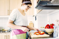 Smiling woman cutting red bell pepper at kitchen counter - ASTF02757