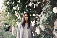 Portrait of happy young woman standing by tree bearing white flowers in park - ASTF02787