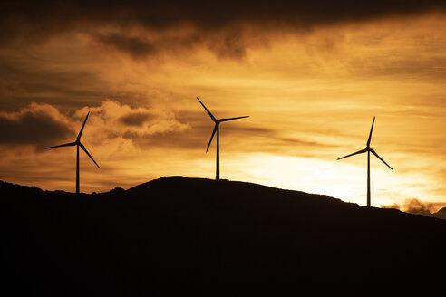 Spain, Andalusia, Tarifa, wind wheels on mountain at sunrise - KBF00464