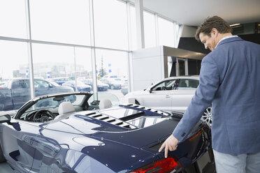 Man looking at convertible in car dealership showroom - HEROF07857