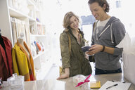 Couple using credit card reader in shop - HEROF07860