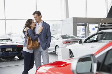 Couple hugging in car dealership showroom - HEROF07878