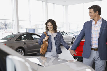 Couple shopping in car dealership showroom - HEROF07884