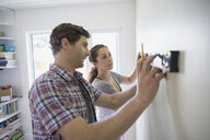 Couple using level tool on living room wall - HEROF07890