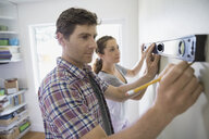 Couple using level tool on living room wall - HEROF07893