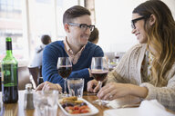 Couple enjoying appetizer and wine at bistro - HEROF07953