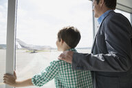 Father and son at sunny airport window - HEROF08007