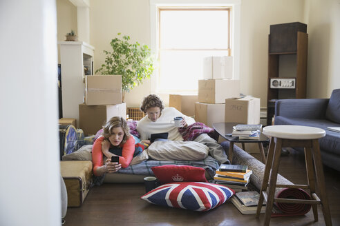 Couple using technology surrounded by moving boxes - HEROF08055