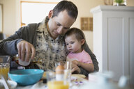 Father and baby daughter enjoying breakfast at table - HEROF08058