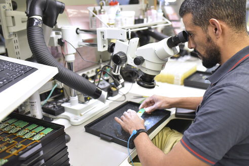 Man using a microscope for the quality control in the manufacturing of circuit boards for the electronics industry - LYF00879