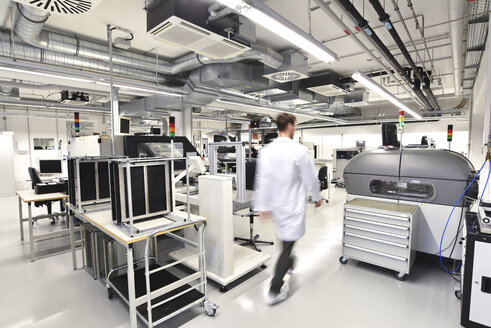 Man walking in a factory for manufacturing of circuit boards for the electronics industry - LYF00903