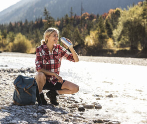 Austria, Alps, woman on a hiking trip having a break at a brook - UUF16510