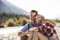 Austria, Alps, happy couple on a hiking trip having a break at a brook - UUF16525