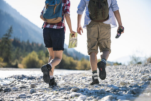 Austria, Alps, couple on a hiking trip with map and binoculars - UUF16528
