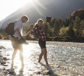 Austria, Alps, couple on a hiking trip wading in a brook - UUF16534