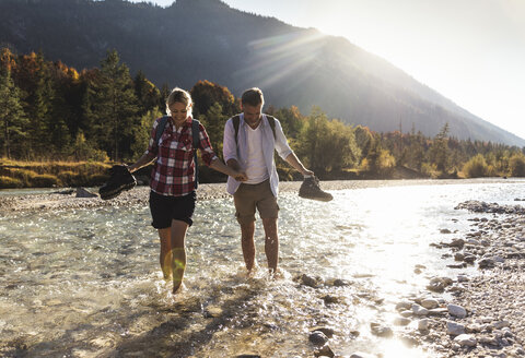 Austria, Alps, couple on a hiking trip wading in a brook - UUF16537
