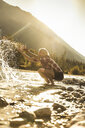 Austria, Alps, happy woman on a hiking trip splashing with water at a brook - UUF16543