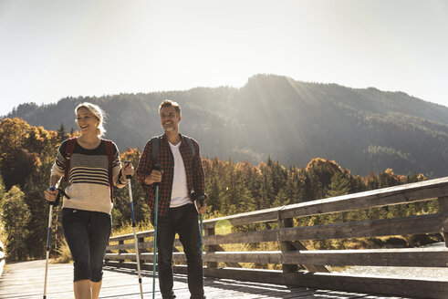 Austria, Alps, happy couple on a hiking trip crossing a bridge - UUF16552