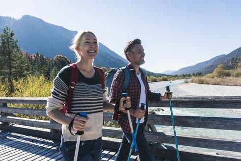 Austria, Alps, happy couple on a hiking trip crossing a bridge - UUF16555