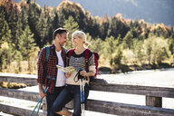 Austria, Alps, happy couple on a hiking trip with map on a bridge - UUF16561