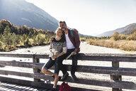 Austria, Alps, couple on a hiking trip having a break on a bridge - UUF16570