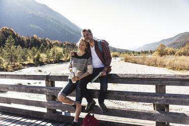 Austria, Alps, couple on a hiking trip having a break on a bridge - UUF16570