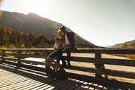 Austria, Alps, couple on a hiking trip having a break on a bridge - UUF16573