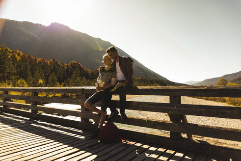 Austria, Alps, couple on a hiking trip having a break on a bridge - UUF16573