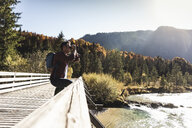 Austria, Alps, man on a hiking trip looking through binoculars - UUF16579