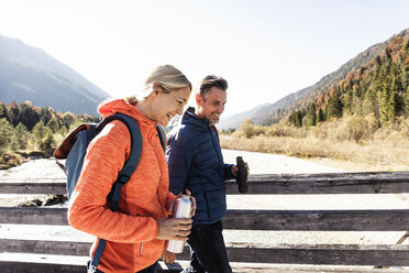 Austria, Alps, happy couple on a hiking trip crossing a bridge - UUF16582