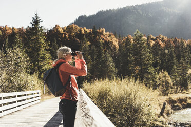 Austria, Alps, woman on a hiking trip looking through binoculars - UUF16585