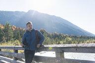 Austria, Alps, man on a hiking trip standing on a bridge with binoculars - UUF16588