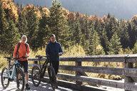 Austria, Alps, couple with mountain bikes crossing a bridge - UUF16591
