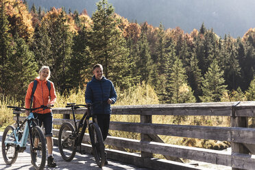 Austria, Alps, couple with mountain bikes crossing a bridge - UUF16591
